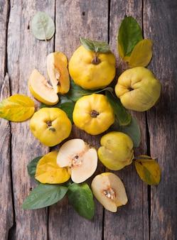 熟した大きなマルメロの果実と茶色の木製のテーブルに晩秋に緑の葉を持つスライス。上面図