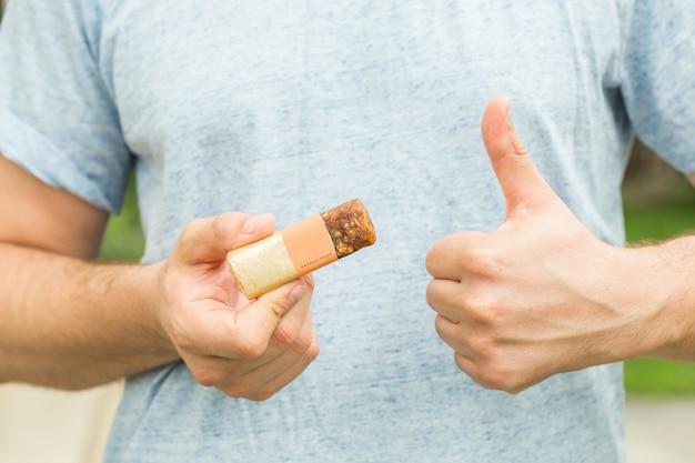 エネルギッシュなシリアルを食べているアメリカ人の男は、手と指を横に向けて非常に幸せなバー