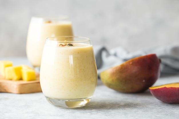 マンゴーラッシー、ヨーグルトまたはスムージー。健康的なプロバイオティクスの冷たい夏の飲み物、マンゴーラッシーまたはラッシー、ヨーグルトまたはスムージー。健康的なプロバイオティクスの冷たい夏の飲み物、マンゴー飲料