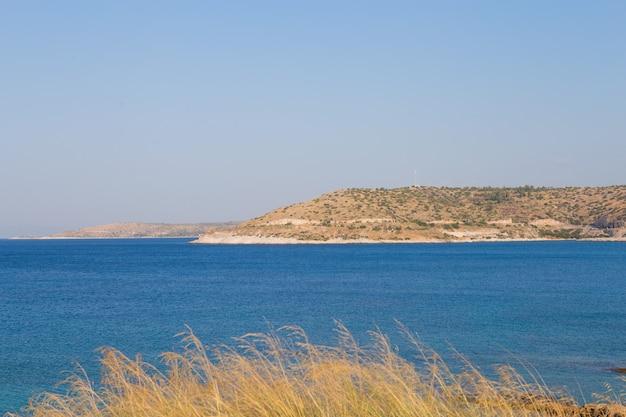 澄んだ青い水、金色の砂、カラフルなボート、山の美しいビーチの眺め。ギリシャとイオニア海の夏の風景。