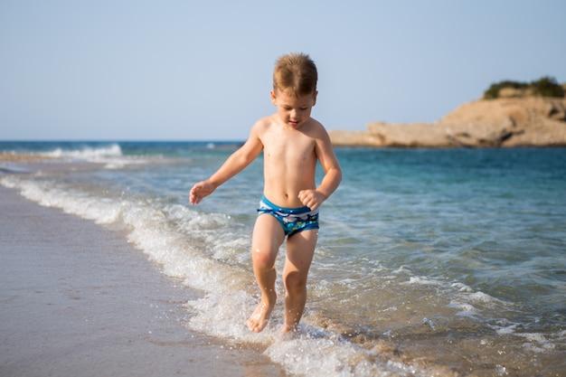 幸せな気分。海の少年。健康な子供時代。幸せな少年は海の水で跳ねます。暖かい気候での楽しいゲーム。