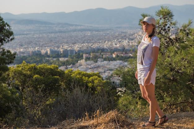 晴れた日に美しい笑顔で遊び心と屈託のないキャップで夢のような空気の魅力的な少女の肖像画、アテネリカベトス山、ギリシャの空気で見た。