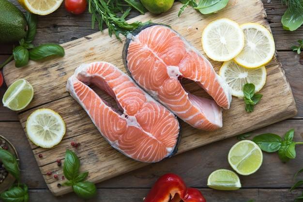 Лосось. сырой стейк из филе лосося с лимонной морской солью и зеленью на белом. закройте