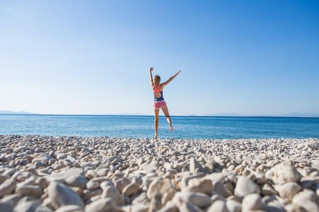 石のビーチでジャンプカジュアルなスタイルで幸せな若い女性。青い空と海のある楽園のビーチでリラックスし、楽しく、休日をお楽しみください。夏休みの女の子。