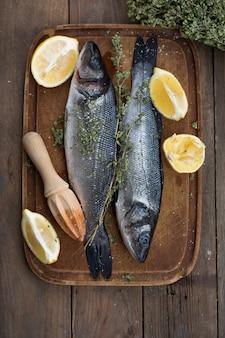 Свежий сырой целый морской окунь. сырая рыба сибас со специями и ингредиентами из трав. вид сверху с копией пространства.