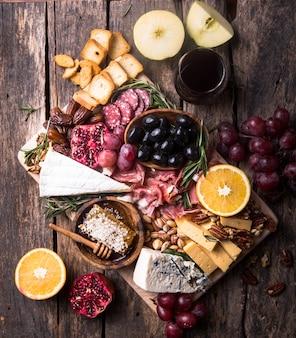 伝統的なイタリアの前菜プレート。木製のまな板に各種チーズ。ブリーチーズ、チェダースライス、ゴゴンゾーラ、クルミ、ブドウ、オリーブ、生ハム、ローズマリー、赤ワインのグラス。上面図