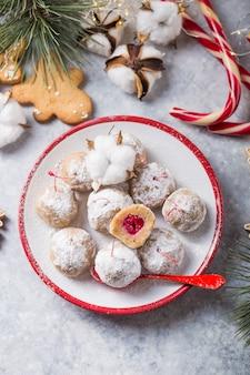 クリスマスデザートテーブルの甘いお菓子。チェリーとビスケットのボール-ロリポップまたはケーキポップ。正月飾りとアップルサイダーの飲み物。幸せなホリデーコンセプト