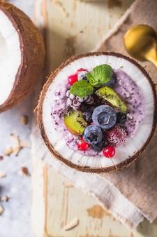 Вкусный аппетитный коктейль из асаи, приготовленный из ежевики и лесных ягод. подается в кокосовой миске. концепция здорового питания чистой еды. замороженный десерт хороший крем.