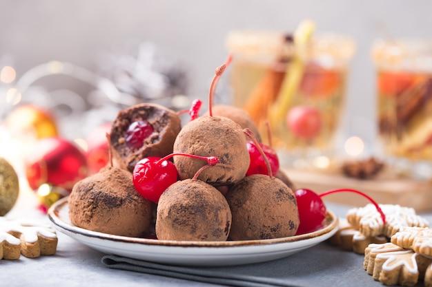 クリスマスデザートテーブルの甘いお菓子。チェリーとビスケットのボール-ロリポップまたはケーキポップ。正月飾りとアップルサイダードリンク。幸せなホリデーコンセプト