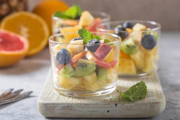 メガネのフルーツサラダ、新鮮な夏の食べ物、健康的な有機オレンジキウイブルーベリーパイナップルココナッツ。上面図