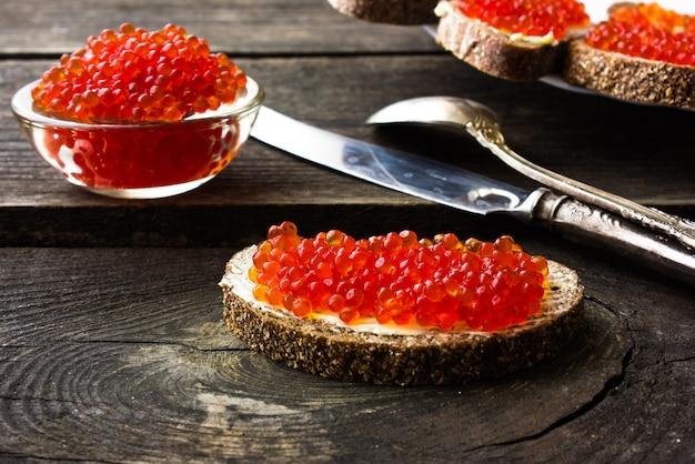 Черный хлеб с красной икрой на сером фоне. бутерброды с красной икрой. здоровая пища.
