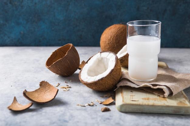 Трещины свежий кокос, молоко и ломтик гайки на бетонном фоне, место для текста пищевые ингредиенты, здоровый образ жизни, рай