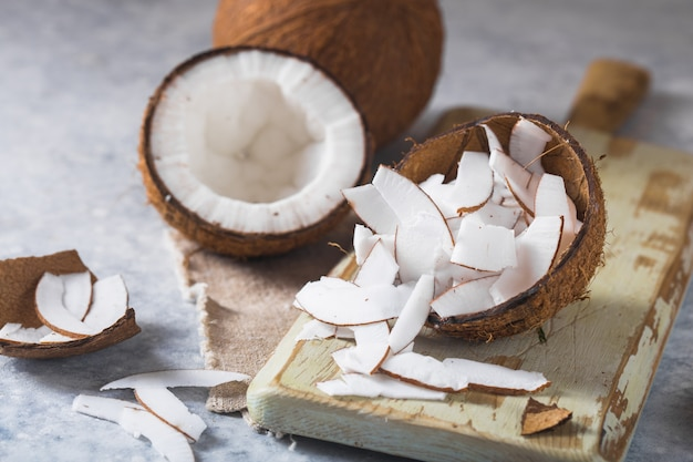 ひびの入った新鮮なココナッツとスライスナッツコンクリート背景、テキスト用食材、健康的なライフスタイル、楽園のスペース