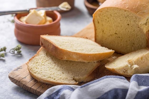 新鮮な自家製のぱりっとしたパンとオリーブオイル、バター、グリーンオリーブ、トップビューでスライス。ベーキング