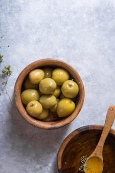 Органическое оливковое масло с зелеными оливками в шаре на белой каменной предпосылке с космосом экземпляра, здоровой едой.