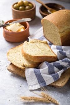 Свежий домашний свежий хлеб с оливковым маслом, маслом и зелеными оливками, вид сверху. выпечка