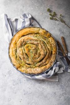 Греческий пирог спанакопита на бетонном фоне. идеи и рецепты вегетарианского или веганского шпинатного пирога из теста фило-теста, нарезанного ломтиками