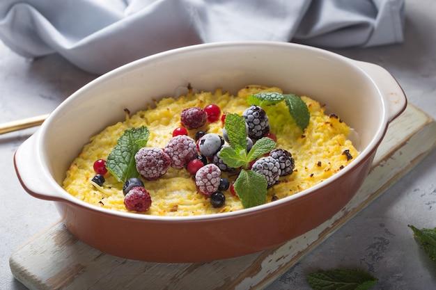 Запеканка из творога, запеченная со свежими ягодами на кухонном столе.
