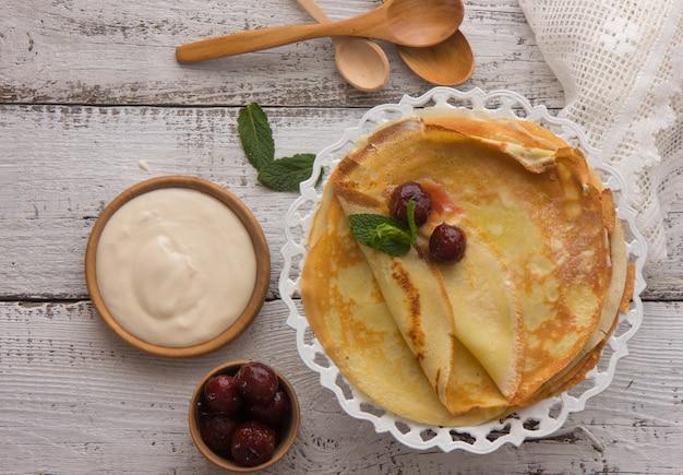 クレープ(ブリニ)と木製の背景、上面に蜂蜜、コピースペース。朝食やデザートに自家製の薄いクレープ。