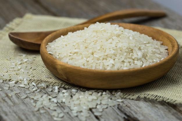 木のスプーンで磨かれた白いご飯。長粒米と丸粒米の背景。米柄米バスマティ米写真生米白米乾米。