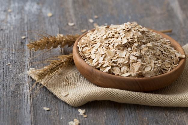 オーツ麦、オーツ麦フレーク、木製ボウルに入れたオーツ麦。健康的な食事、ダイエット、健康的なライフスタイル、減量の概念