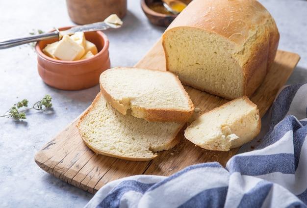 Свежий домашний свежий хлеб и ломтики с оливковым маслом, маслом и зелеными оливками, вид сверху. концепция выпечки