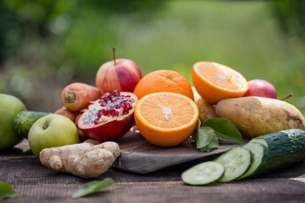 さまざまな果物または野菜と緑の自然の上のテーブルの上の果物
