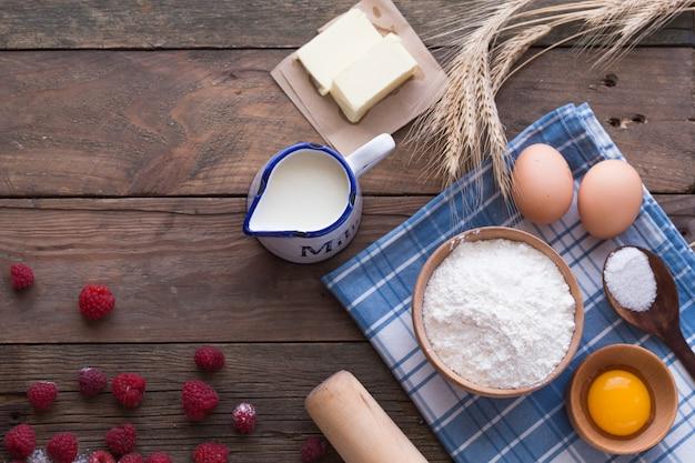料理とベーキングのコンセプト。暗い背景に食材を焼きます。卵、小麦粉、小麦の穂とロール。ホームベーキング、自家製料理フラットレイアウトトップビュー