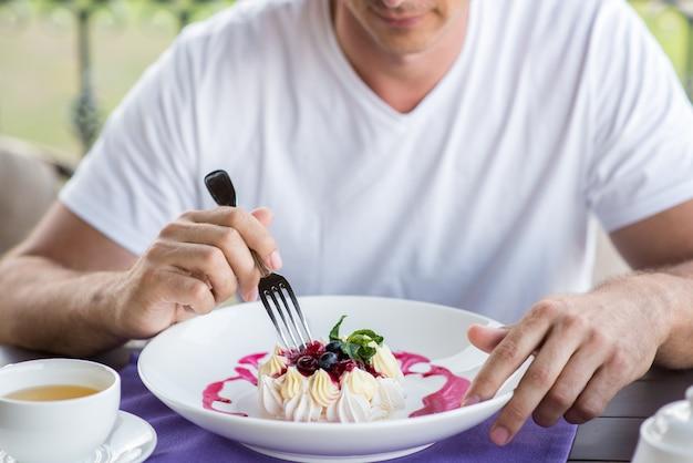 フォークケーキパブロバで食べるハンサムな若い男