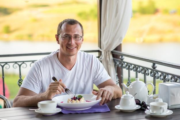 カフェパブロバを食べるカフェでハンサムな笑みを浮かべて男