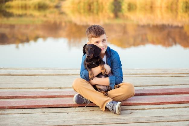 屋外の黒犬を抱き締める少年。友情、愛と関係の概念