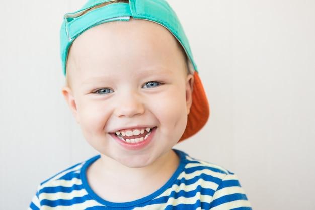 Улыбающийся мальчик в полосатой футболке.