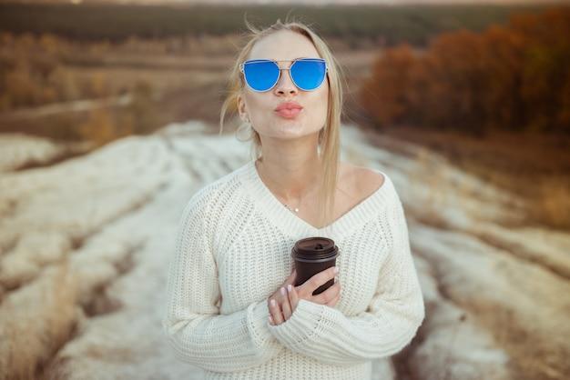 Молодая девушка в солнечных очках и с кофе в осеннем парке