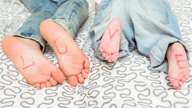 Ноги. брат и сестра отдыхают на кровати.