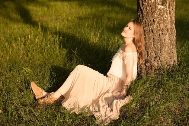 Молодая женщина сидит возле дерева на траве летом