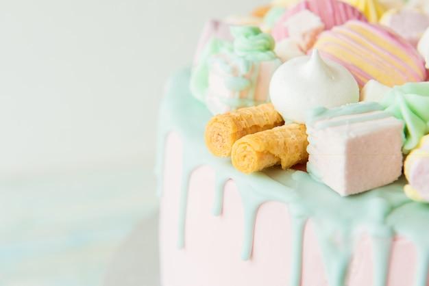 Розовый торт с печеньем, макаронами и зефиром.