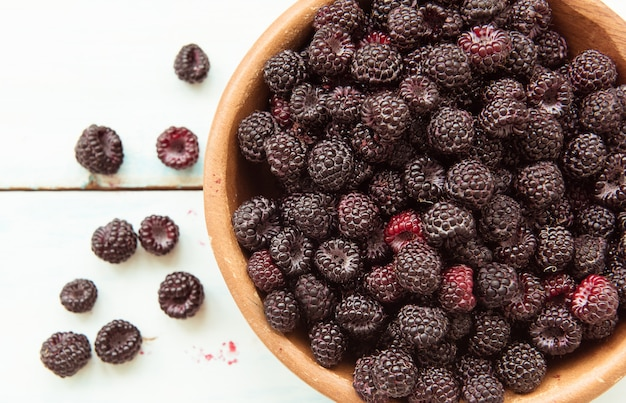 Спелые свежие ягоды ежевики в деревянной миске на столе. вид сверху