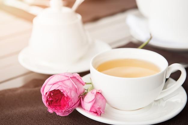 Чашка белого чая с чайником и сахарницей на столе