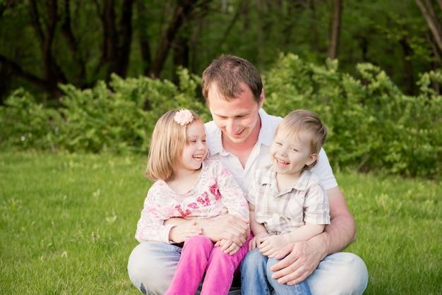 Отец и дети играют вместе на открытом воздухе.
