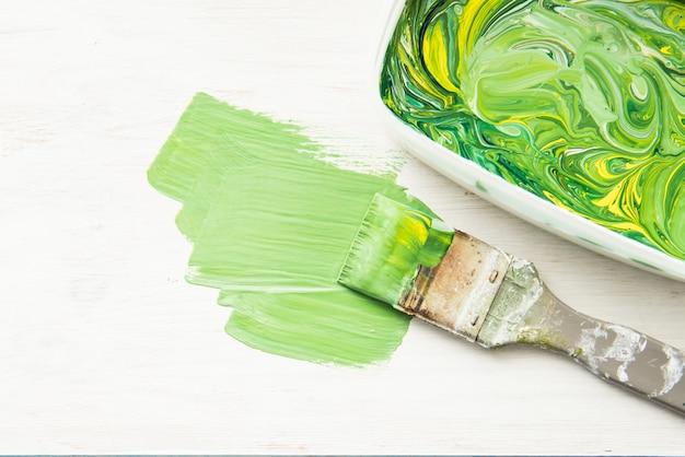 Кисть зелено-желтой краской на белом