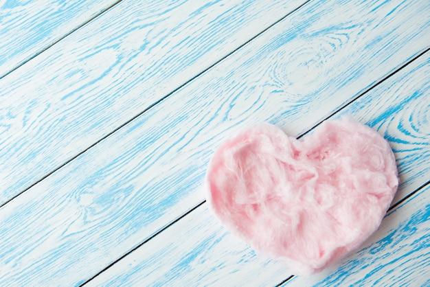 青い木製のテーブルにハートの形の甘い綿菓子。コピースペース