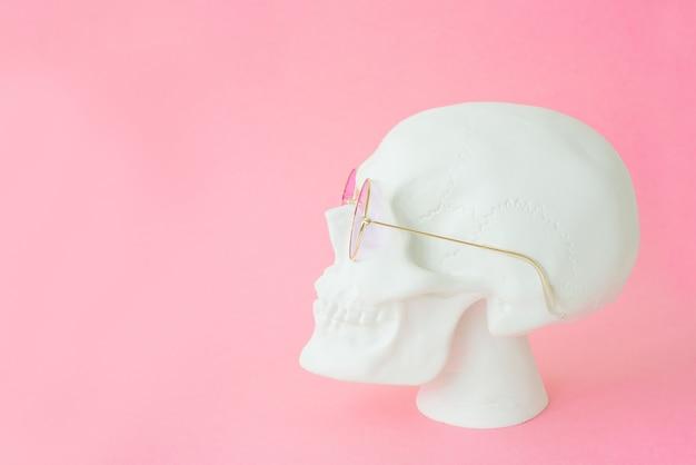 Белый человеческий череп с розовыми очками. закрыть