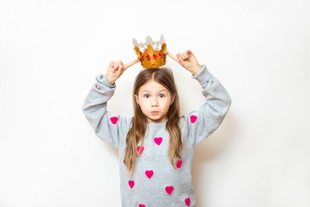 Положительный ребенок девочка примеряет корону на голову