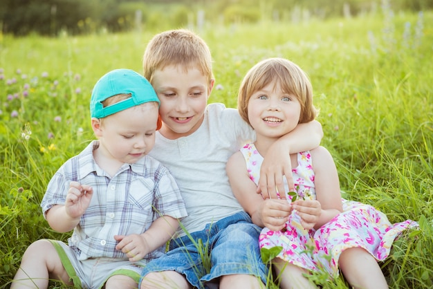 外の緑の芝生に座って抱いて幸せな子供