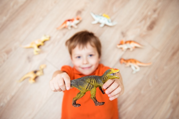 恐竜のコレクションで床に横たわっている男の子。セレクティブフォーカス