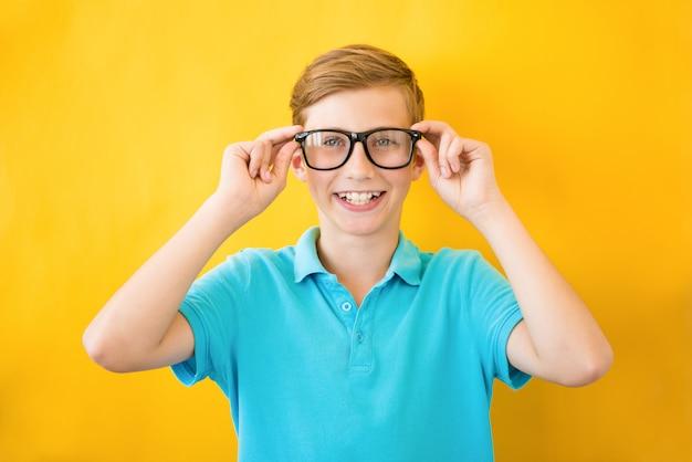 ハンサムな十代の少年は眼鏡をかけています。ビジョンと医学の貧弱な概念