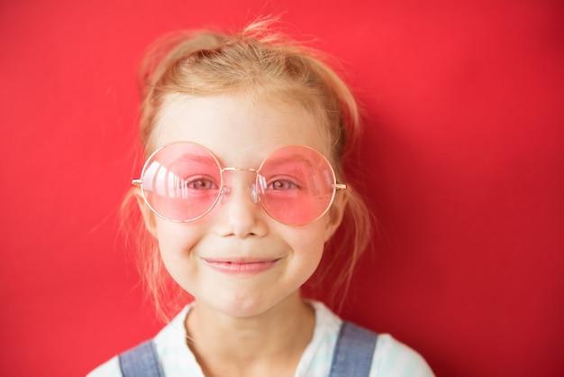 赤の大きな丸いピンクのメガネの少女の笑顔