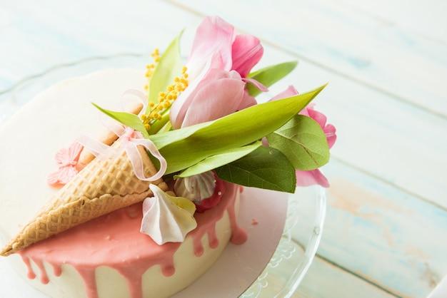 白のビスケットケーキにピンクのチューリップの花束