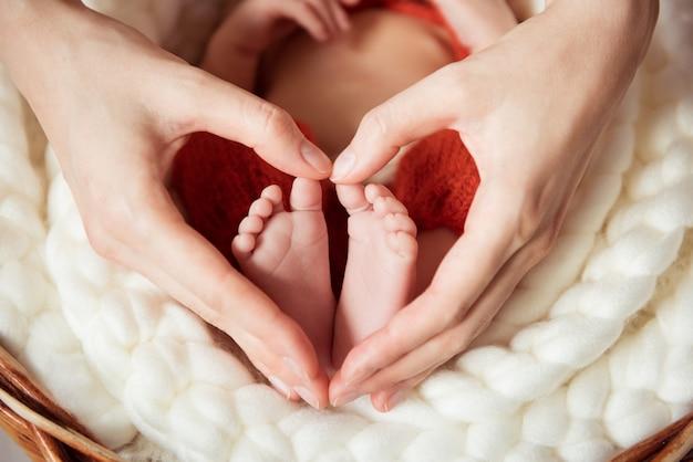 生まれたばかりの赤ちゃんの足を握るハート型のママの腕