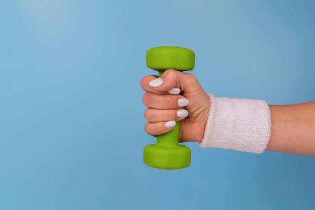 緑のダンベルを保持している白い爪を持つ人
